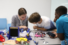 A team works through the challenge of combining building hardware, wiring, the electronics, and programming the behavior of the robot.