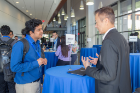 Industry member talks to grad student at networking reception.