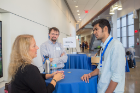 Industry members talk to grad student at networking reception.
