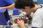 A student works on the circuit board of his robot.