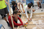 A group of students sets up their robots for the next round of testing.