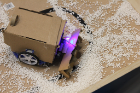 A snow plow robot, complete with accent lighting, moves artificial snow in the test area.