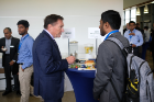 Keynote speaker Mark Santoro, a principal engineering fellow for Space and Airborne Systems in the Hardware Engineering Center at Raytheon, talks with a student during the Career Preparation Reception. Santoro is an electrical engineering alumnus of UB.