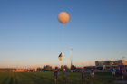 A parachute is placed between the instruments, held by the student on the left, and the balloon to ensure the instruments land safely and are recoverable.