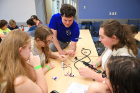UB aerospace engineering student Andrew Dianetti (center) puts together a radio with (from left) Shannon Lynch, Kylie Naylor, Annabella Bogart and Sarah Cumming. The girls are from Troop 981 at Sweet Home High School.