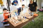 Nathan Lotz (left) and Joseph Ray (center) of Pack 104 use catapults to launch small stuffed objects toward a target in the STEM tent. Offering advice is activity leader Joe Cercone from Troop 5.