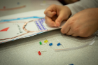 "LED diodes add some extra sparkle to a child's artwork at the ""Paper Circuits"" activity."