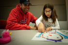Paschal Frisina watches his daughter, Liliana, work with copper tape to make a circuit to light up her snowman.