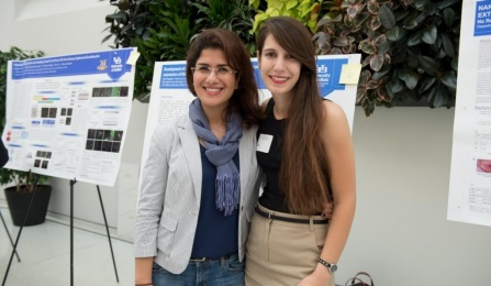 2 students posing front of their research posters at symposium