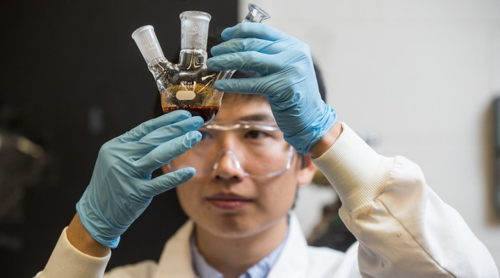 CBE student looks at a sample in the lab.