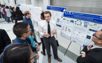 Student presenting poster to two students at graduate symposium