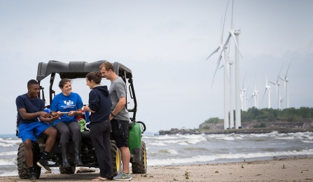 University at Buffalo students stand with a professor reviewing samples on a beach. Windmills are in the background.