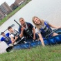 Students in a concrete canoe on the water near the shoreline.