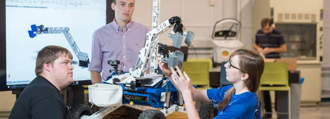 students in lab working on robot