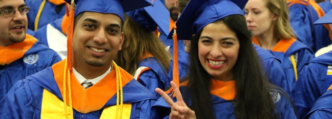Two SEAS students at commencement, one showing the peace sign.