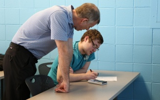 instructor helps student.