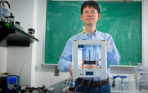 Chi Zhou, assistant professor of industrial and systems engineering, holds a 3D printer.