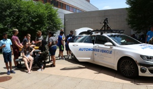 Students checking out UB's autonomous vehicle.