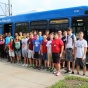 group photo of campers in front of a UB Stampede bus