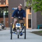 Nick stone riding tricycle outside Jarvis Hall.