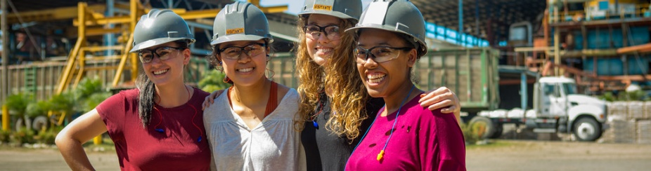 Four women in hard hats touring a Sugar Mill in Costa Rica as part of an Environmental Engineering class researching sustainability.