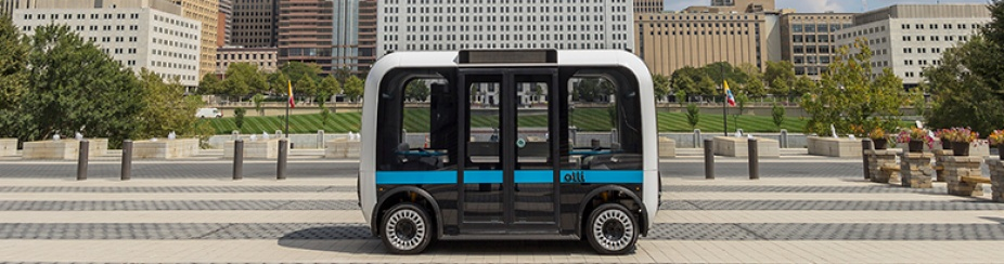 Autonomous shuttle driving along a citiscape.