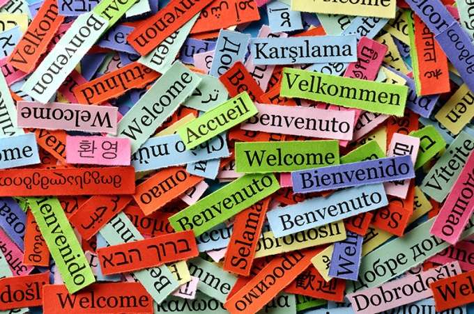 "The world ""Welcome"" written on papers in several different languages."