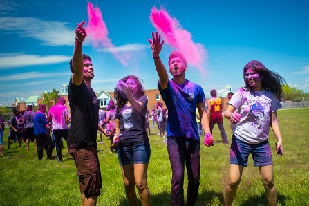 Indian students throwing pink color into the sky on UB's North Campus