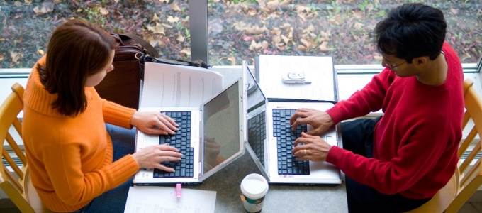 Two students work on laptops.