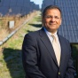 Amit Goyal standing in front of solar array on UB campus.