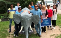 Lori posing with faculty and students outside of the student union with elephant model