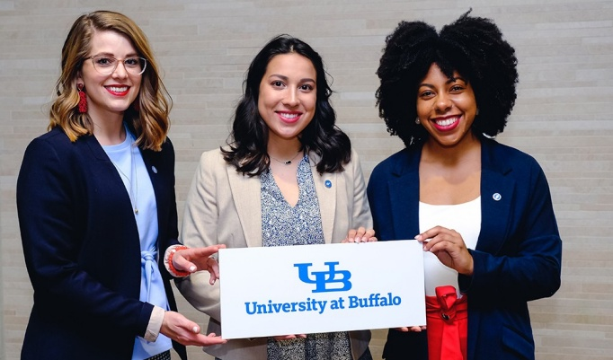 UB undergraduate students Kelley Mosher, Isabel Hall and Danielle Vazquez at Worlds Challenge Challenge. The three students are holding a sign that reads University at Buffalo with UB's logo.