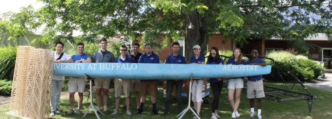 UB ASCE poses with the seismic design team's tower and the club's canoe.