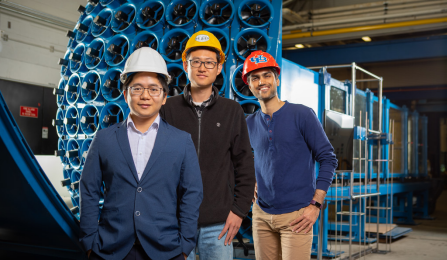 Teng Wu, Shaopeng Li and Shivam Mishra stand in front of the wind tunnel.