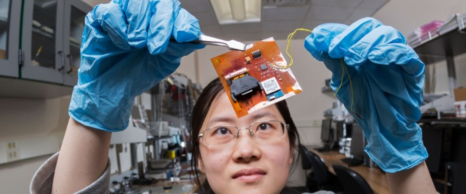 The Empire Innovation Program. Asian woman holds up small motherboard with tweezers and looks up at it in science lab.