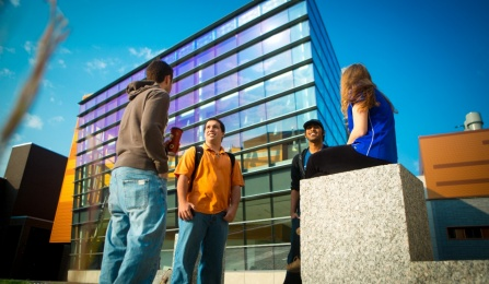 Four students chat in front of Davis Hall.