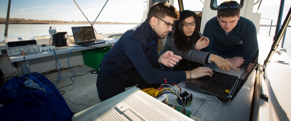 students on boat on Lake Erie researching underwater internet.
