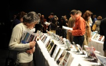 Individuals browse rows of tables displaying books