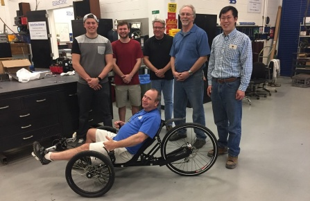 Curt Senf shows off his new trike designed by mechanical engineering students Caleb Walters and Austin Powers for their senior design project.