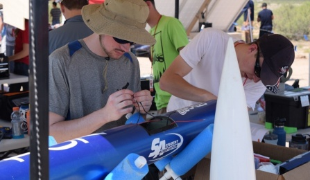 Gabriel Surina and Jacob Henry make adjustments to the avionics system.