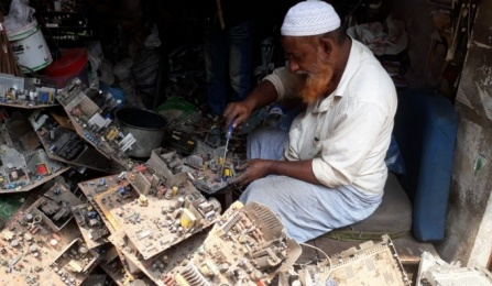 Photo of man in Bangladesh removing e-waste from a computer motherboard.