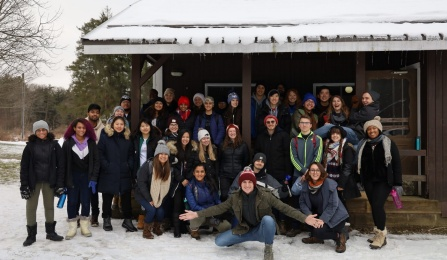 Group photo of ESW at a cabin outside in the snow.