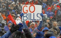 "A photo of a Buffalo Bills fan holding a sign that reads, ""Go Bills."""