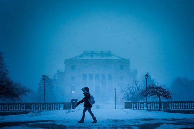 Student walks across campus during a December snow storm.