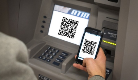 Image of person holding smartphone in front of ATM with QR codes on smartphone and ATM.