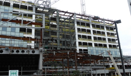 The image shows shows a large hospital being constructed with a ductile moment resisting steel frame (on top of base isolators, but the base isolation system is not shown in the photo).