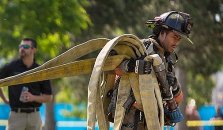firefighter carries hoses during a drill.