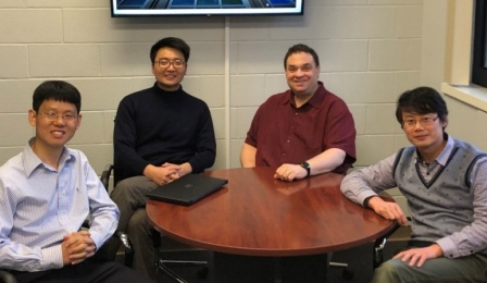 From left to right, seated at a table, are Chi Zhou (UB), Shenqiang Ren (UB), Mark Swihart (UB), and Donghui Zhao (Unifrax).
