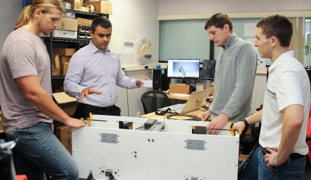 Smart Walls Construction founder and Chief Technology Officer Jorge Cueto standing with UB engineering students Christopher Borders, Derek Roback and Albert Shaw around a prototype of the company's smart walls technology.