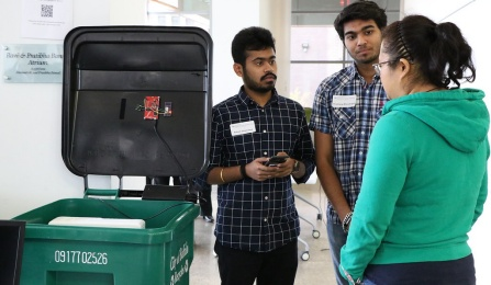Three UB students stand around a garbage bin outfitted with sensors so it's connected to the internet.